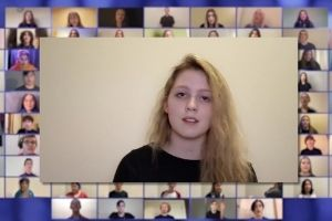 a screenshot of a young woman singing as part of an online choir performance