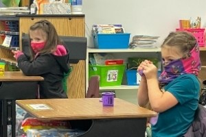two girls in a school classroom wearing masks